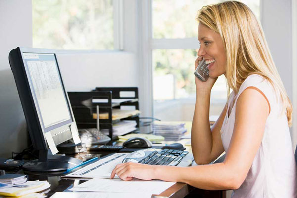 A woman using the computer while talking on the phone.
